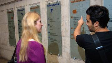 Ein Mann und eine Frau betrachten Wegweiser (Bild: Costa Belibasakis/FH Köln)