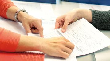 Bildausschnitt einer Beratungssituation, Hände überreichen ein Formular (Bild: Thilo Schmülgen/FH Köln)