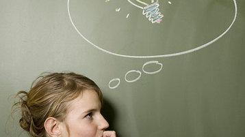 Eine junge Frau steht vor einer Tafel, auf der eine Glühbirne in einer Denkblase zu sehen ist und grübelt (Bild: iStock)