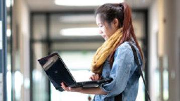 Eine Studentin steht mit einem Laptop im Flur (Bild: Thilo Schmülgen/FH Köln)